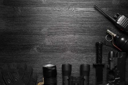 Black airsoft gun, walkie talkie radio station, binoculars and knife on the black flat lay background with copy space. 版權商用圖片