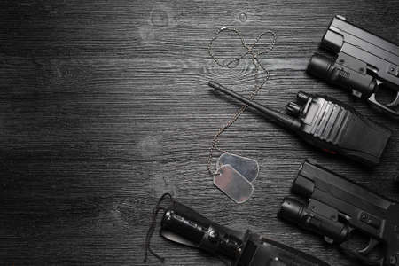 Black airsoft gun, walkie talkie radio station and knife and soldier badge on the black flat lay background with copy space.