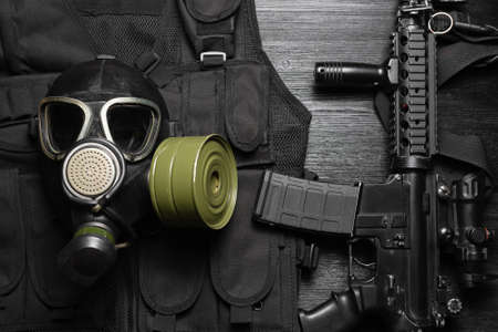 Gas mask and airsoft rifle on the black flat lay background.