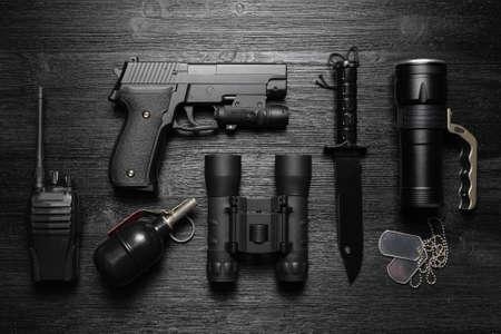 Black airsoft gun, walkie talkie radio station, binoculars, knife and soldier badge on the black flat lay background. 版權商用圖片