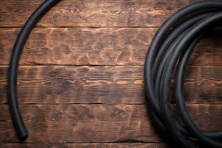 Old rubber water hose on the brown wooden floor background with copy space.