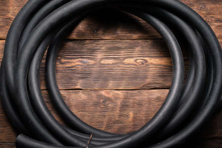 Old rubber water hose on the brown wooden floor background. 版權商用圖片