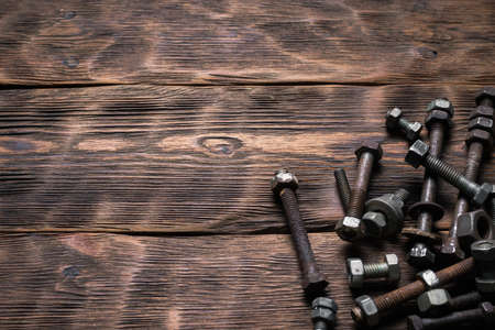 Old rusty bolts and nuts on the carpenter workbench background with copy space.