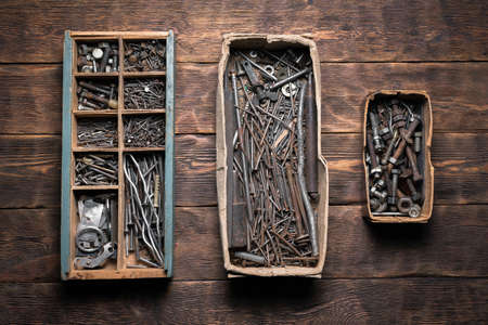 Rusty nails, nuts and bolts in the storage boxes on the old ooden carpenter workbench flat lay background. 版權商用圖片