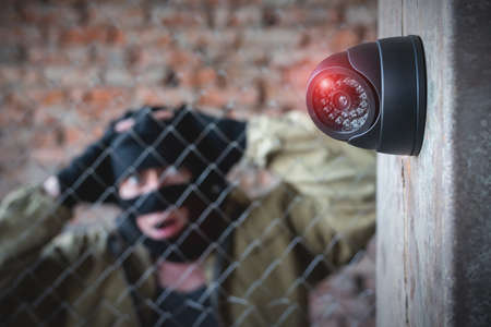 Security camera on the wall close up and confused robber in the mask behind the fence concept background.