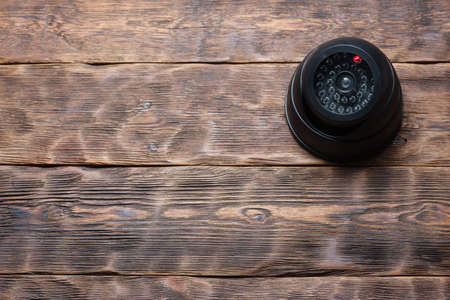 Security camera on the wooden wall background with copy space. 版權商用圖片