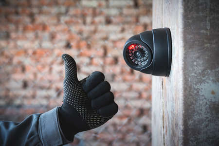 Security camera on the wall close up and worker hand that shows a thumbs up gesture. Best video surveillance service concept.