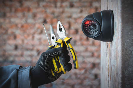 Security camera on the wall close up and worker hand with a work tools. Video surveillance system maintenance concept. 版權商用圖片