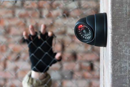 Security camera on the wall close up and robber hand behind the fence concept background.