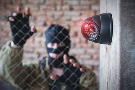 Security camera on the wall close up and robber in the mask behind the fence concept background. 版權商用圖片