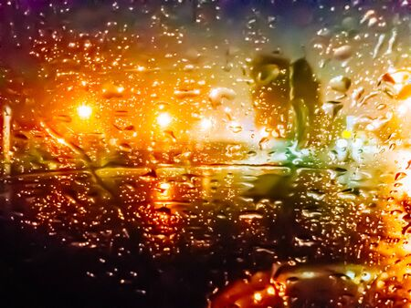 blurred image of lights of the city at night through the rain drops on the glass Stock Photo