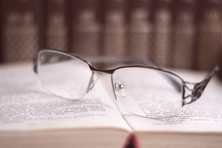 volumes: Glasses on open book on background book volumes