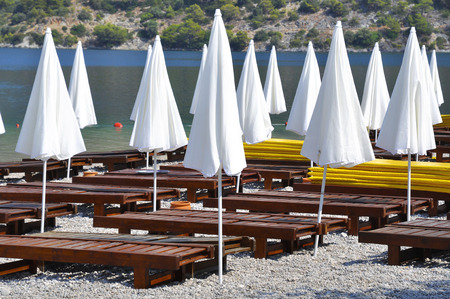 loungers: Closed white beach umbrellas and wooden loungers on a deserted beach
