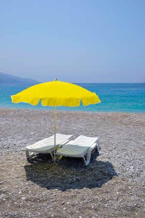 loungers: Yellow parasol and two white sun loungers on the beach Stock Photo