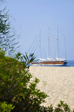 pleasure boat: Pleasure boat docked next to the sandy beach on a sunny day