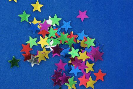 Glittering multicolored stars on blue background Stock Photo