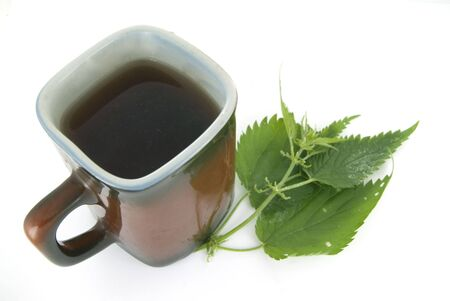A cup of herbal tea and a nettle