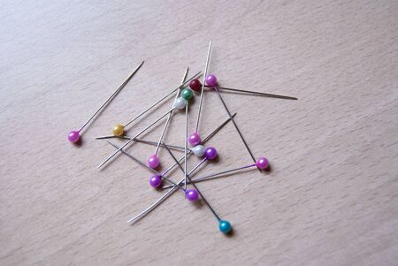 A heap of sewing pins on wood Stock Photo