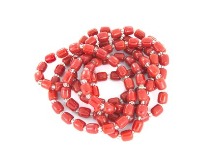 Red plastic necklace rollde up in a coil