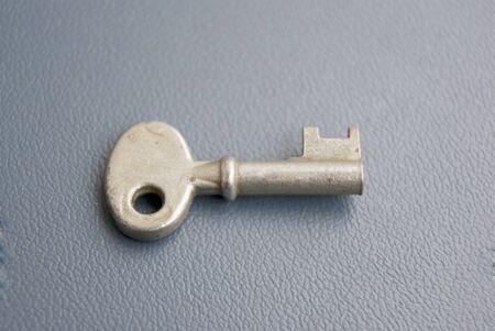 Vintage old worn-out key on blue