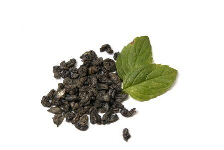 Gunpowder green tea with fresh mint leaves on white background