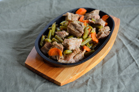 Stewed meat served in a frying-pan cooked with vegetables Stock Photo