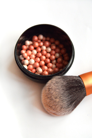 Blush in balls in a plastic round open box with a thick brush shown Stock Photo