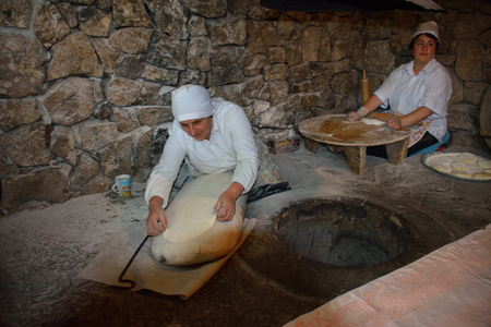armenian woman: Women cooking traditional armenian lavash. One woman is spreading bread over the special soft pillow
