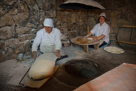 armenian woman: Ready to bake traditional armenian lavash. A woman is spreading dough over special pillow