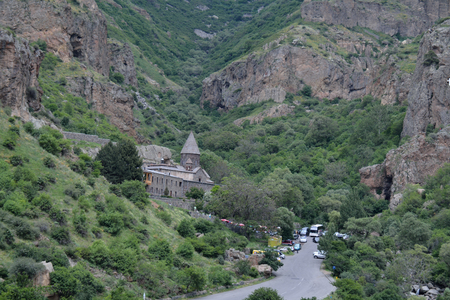geghard: Geghard monastery in the Armenian mountains, with the nearby road and the tourists coming