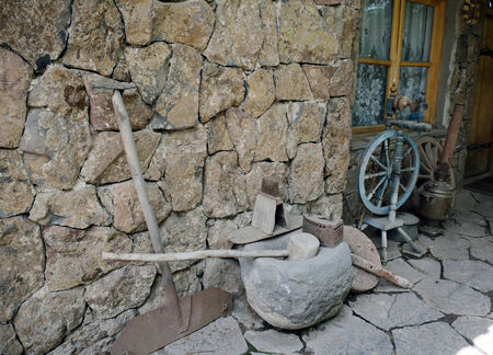 ancient tools and everyday objects next to the wall of the old house Stock Photo