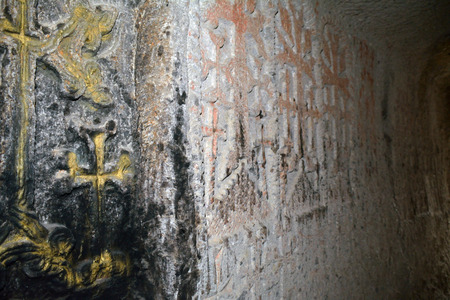geghard: The church wall in the Geghard monastery with dyed and carved crosses.
