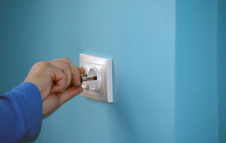 arm of the electrician fixing a socket cover on the wall Stock Photo