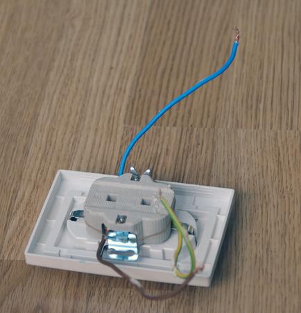 dismantled: Dismantled plastic socket lying on the wooden floor Stock Photo