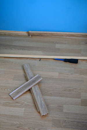 baseboard: Part of the wall, baseboard and a screwdriver on the floor