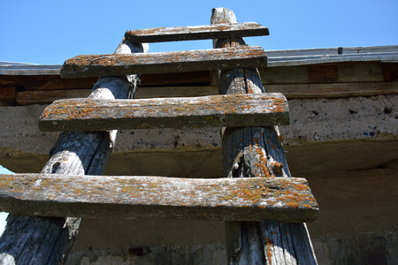 Old wooden ladder pointed to the sky outdoors