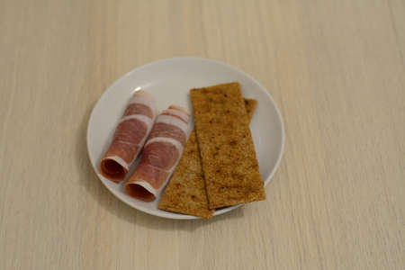crisps: thin slices of prochutto ham with rye crisps on the plate