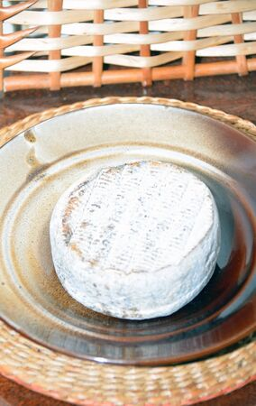 riped: Selles sur Cher cheese riped in charcoal on the plate Stock Photo