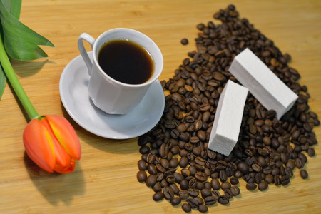 long beans: coffee in a cup and coffee beans with a fresh tulip and marshmellow closeup