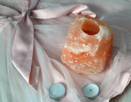 salt lamp: orange salt lamp with candles on pink vintage laces Stock Photo