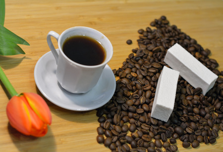 mocca: hot mocca in a cup, coffee beans, vanilla pastille and a tulip on the table Stock Photo