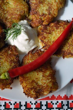 hashbrown: draniki - thin potato pancakes - on a plate with sour cream closeup