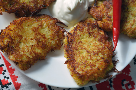 hashbrown: closeup of thin potato pancakes with hot papper and sour cream on a plate Stock Photo