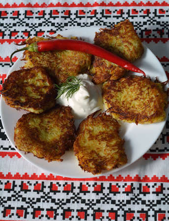 hashbrown: thin potato pancakes with sour cream on a traditional ukrainian towel