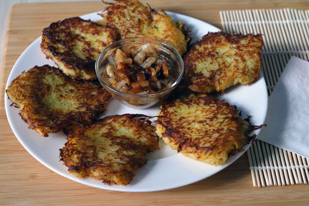 hashbrown: potato pancakes with lard and fried onion on white plate