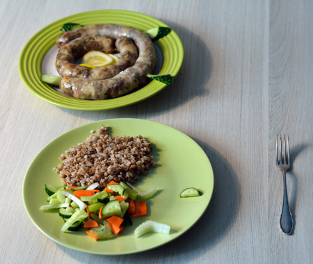 hot homemade pork sausage served with garnish of boiled buckwheat with fresh vegetable salad