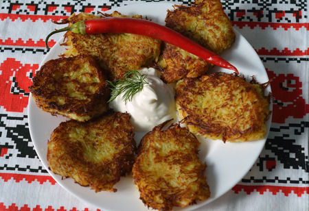 hashbrown: draniki - thin potato pancales - served with sour cream amd a hot pepper Stock Photo