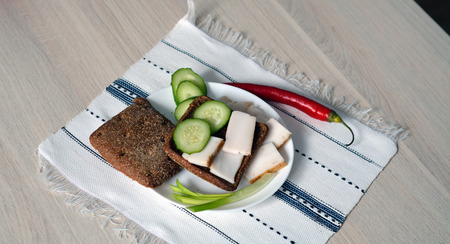 lard: sandwich of cucumber and lard with rye bread on the plate