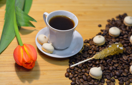 hot mocca in a cup, coffee beans, small pastry, sugar stick and a tulip on the table Stock Photo