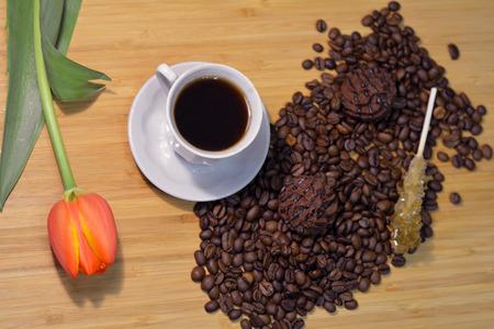 cafe bombon: taza de caf� caliente con un tulip�n fresca, granos de caf�, el az�car y el palo de un bomb�n de chocolate en la parte superior